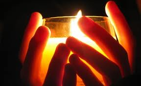 Picture of hand-held lit candle glass.