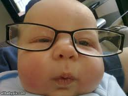 Close up photograph of a baby's face with eyeglasses.